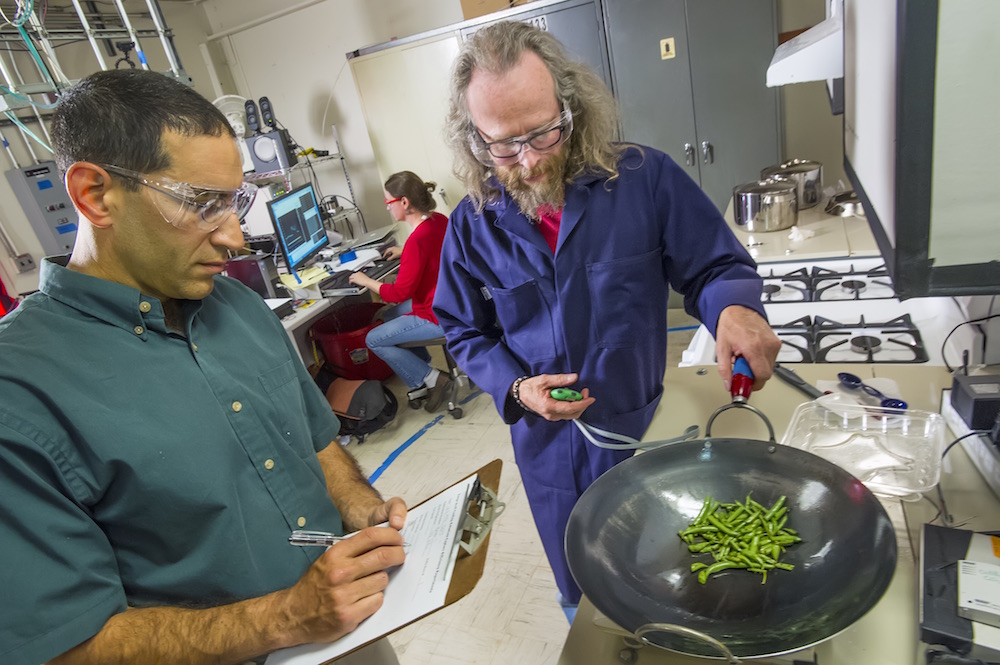 Berkeley Lab researchers Brett Singer (left) and Woody Delp fry green beans to generate particles for testing air quality monitors. (Credit: Roy Kaltschmidt/Berkeley Lab)